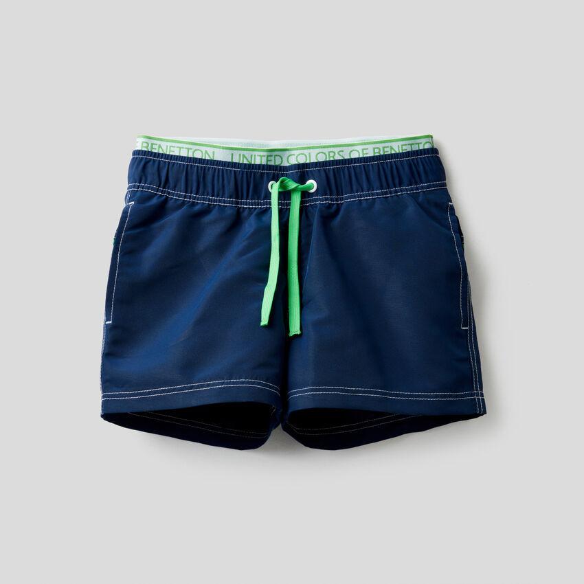 Swim trunks with elastic logo